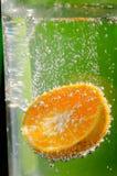 Éclaboussement orange dans l'eau claire Image stock
