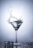 Éclaboussez du glaçon en verre de martini d'isolement Photographie stock