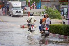 Éclaboussez en une moto comme elle passe par des eaux d'inondation Images libres de droits