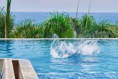 Éclaboussez l'eau dans la piscine d'une personne penchée Piscine extérieure sur la paume et la mer de fond Vue arrière photo libre de droits