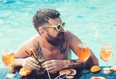 Éclaboussure d'été des cocktails et du fruit colorés éclaboussure d'été, homme barbu buvant dans la piscine photos libres de droits