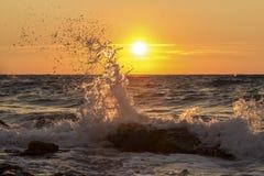 Éclaboussure d'onde au coucher du soleil Photographie stock libre de droits