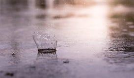 Éclaboussure de baisse de pluie sur la surface de l'eau, quand il pleut photographie stock