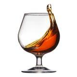 Éclaboussure de cognac en verre sur le fond blanc images libres de droits