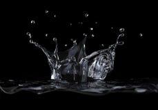 Éclaboussure de couronne de l'eau vue d'un côté, sur le fond noir. image libre de droits