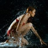 Éclaboussure de femme et d'eau dans l'obscurité Photos libres de droits