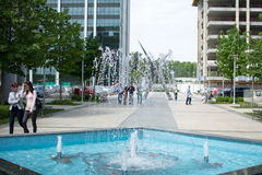 Éclaboussure de fontaine de ville, avec des personnes marchant tout près Photos libres de droits