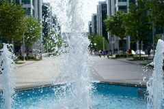 Éclaboussure de fontaine de ville, avec des personnes marchant tout près Images libres de droits