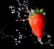 Éclaboussure de fraise dans le noir Photos libres de droits