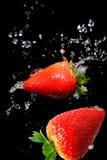 Éclaboussure de fraise dans le noir Photographie stock libre de droits