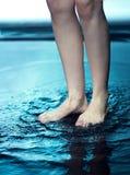 Éclaboussure de l'eau chez le pied de la femme Images stock