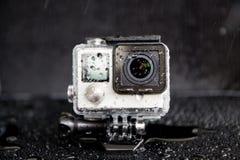 Éclaboussure de l'eau de plan rapproché sur l'appareil-photo extrême dans imperméable Images stock