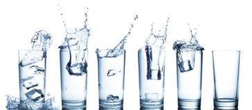 Éclaboussure de l'eau en verres d'isolement sur le blanc Photos stock