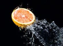 Éclaboussure de l'eau sur le pamplemousse Images stock