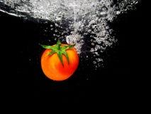 Éclaboussure de tomate dans l'eau, Bacground noir Image stock