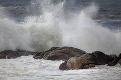 Éclaboussure de vague contre des roches photo stock