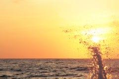 Éclaboussure de vague de mer au coucher du soleil Photo stock