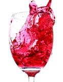 Éclaboussure de vin rouge d'un verre Images stock