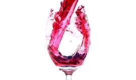 Éclaboussure de vin rouge d'un verre Photos stock