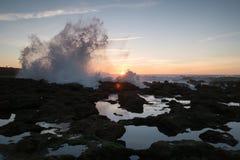 Éclaboussure des ressacs sur un fond de coucher du soleil et de roches photo libre de droits