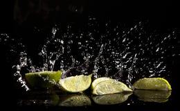 Éclaboussure et limettes de l'eau Photos stock