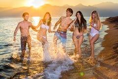 Éclaboussure riante de cinq amis dans l'océan Images stock