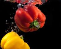 Éclaboussure rouge et jaune de paprika et d'eau. Photographie stock libre de droits