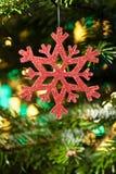 Éclaille artificielle rouge de neige dans un arbre de Noël photographie stock