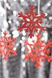 Éclaille rouge de neige sur un fond argenté de scintillement Photo stock