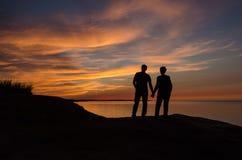 Éclairage arrière des couples tenant des agains coucher du soleil rouge, rayons de soleil de mains photos libres de droits
