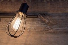 Éclairage de salle de bains avec la cage rustique d'ampoule en métal sur un fond de bois superficiel par les agents photo libre de droits