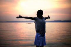 Éclairez la femme à contre-jour prenant une respiration profonde au coucher du soleil Photo libre de droits