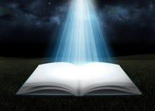 Éclat sur le livre ouvert la nuit Photos stock