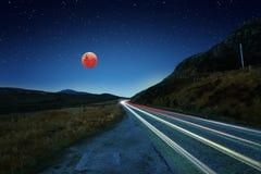 Éclipse superbe de lune de sang bleu et traînées de voiture photographie stock
