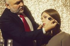 École de maquillage Homme professionnel de visagiste appliquant la poudre sur le visage de fille avec la brosse photos libres de droits
