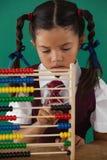 Écolière à l'aide de l'abaque contre le tableau Photographie stock