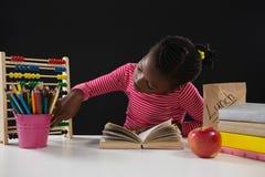 Écolière à l'aide de l'abaque sur le fond noir Images libres de droits