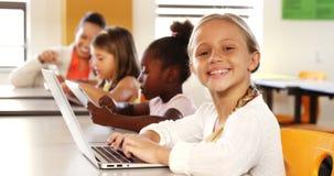 Écolière à l'aide de l'ordinateur portable dans la salle de classe banque de vidéos