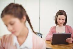 Écolière à l'aide de la Tablette de Digital dans la salle de classe Image libre de droits