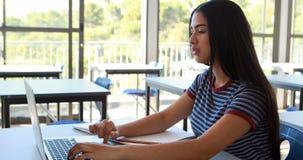 Écolière à l'aide du comprimé numérique et de l'ordinateur portable dans la salle de classe banque de vidéos