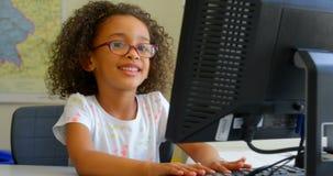 Écolière à l'aide du PC de bureau dans la salle de classe à l'école 4k banque de vidéos