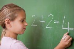Écolière écrivant un numéro Image libre de droits