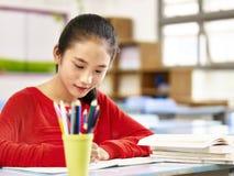 Écolière élémentaire asiatique étudiant dans la salle de classe Photographie stock libre de droits