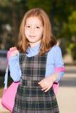 Écolière élémentaire d'âge dans l'uniforme avec le sac à dos photo stock