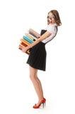 Écolière étonnée sur un fond blanc avec une pile des livres Photo libre de droits