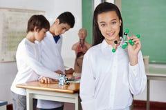 Écolière adolescente tenant la structure moléculaire Images libres de droits
