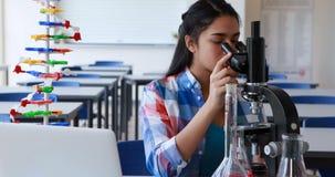 Écolière attentive à l'aide de l'ordinateur portable tout en expérimentant dans le laboratoire banque de vidéos