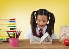 Écolière au bureau devant le fond jaune avec l'abaque et le livre Image libre de droits