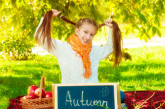Écolière avec des pommes en automne Image stock