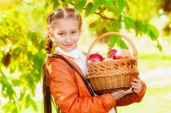 Écolière avec des pommes en automne Photographie stock libre de droits